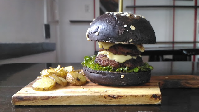 black colored hamburger with chips